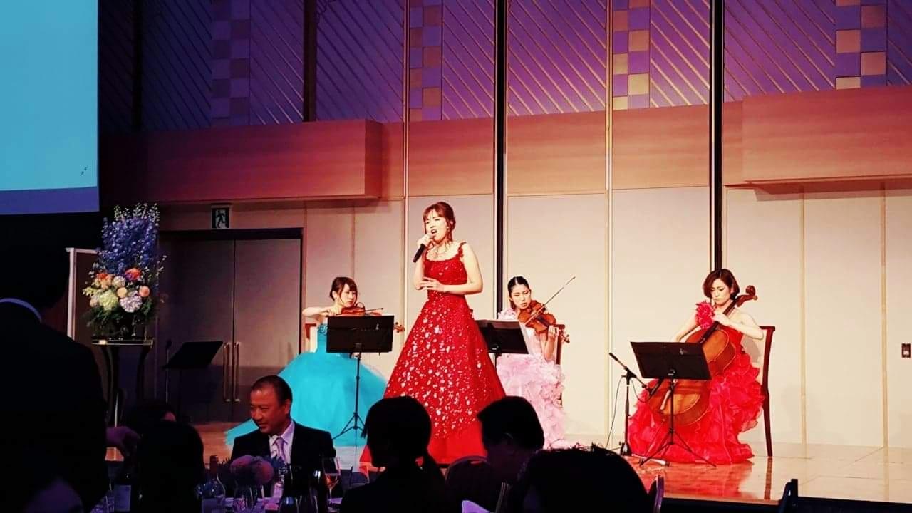 ステージで歌うソプラノ歌手と弦楽