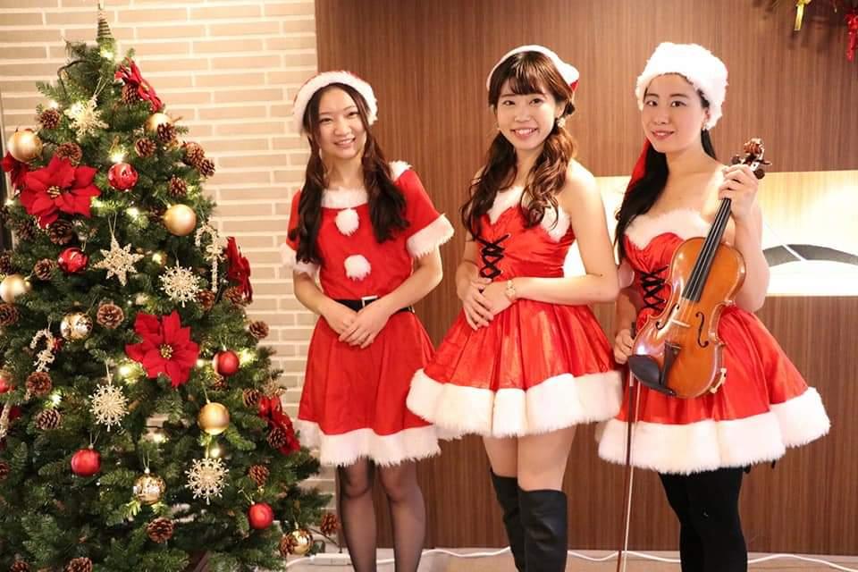 サンタ衣装の演奏家三人