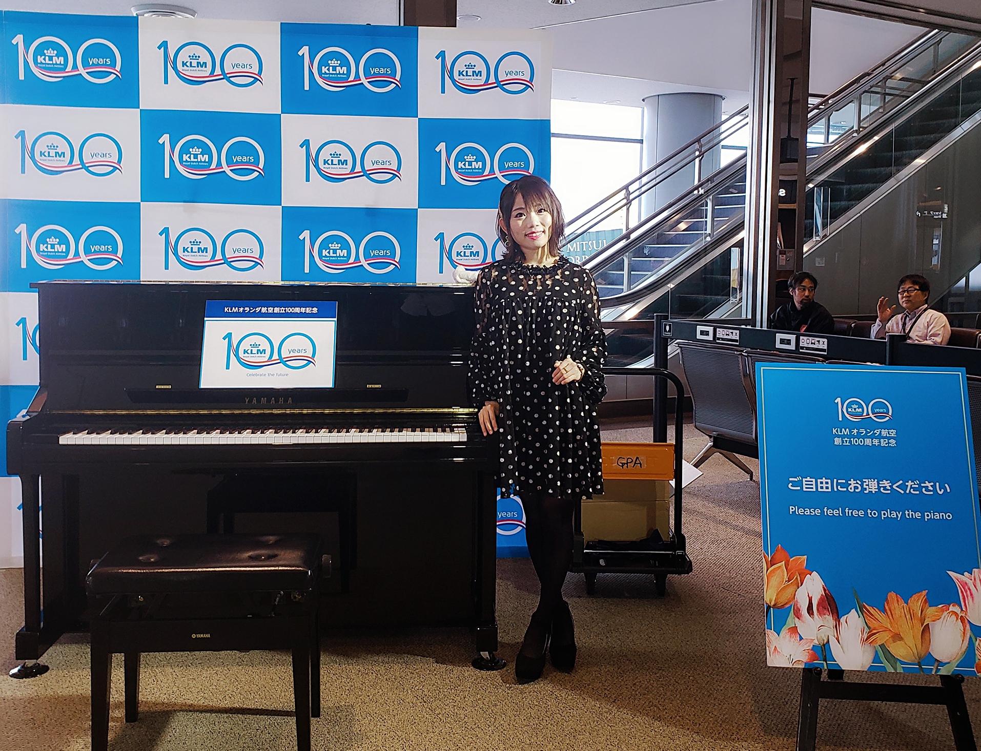 ピアノの脇に立っているピアニスト