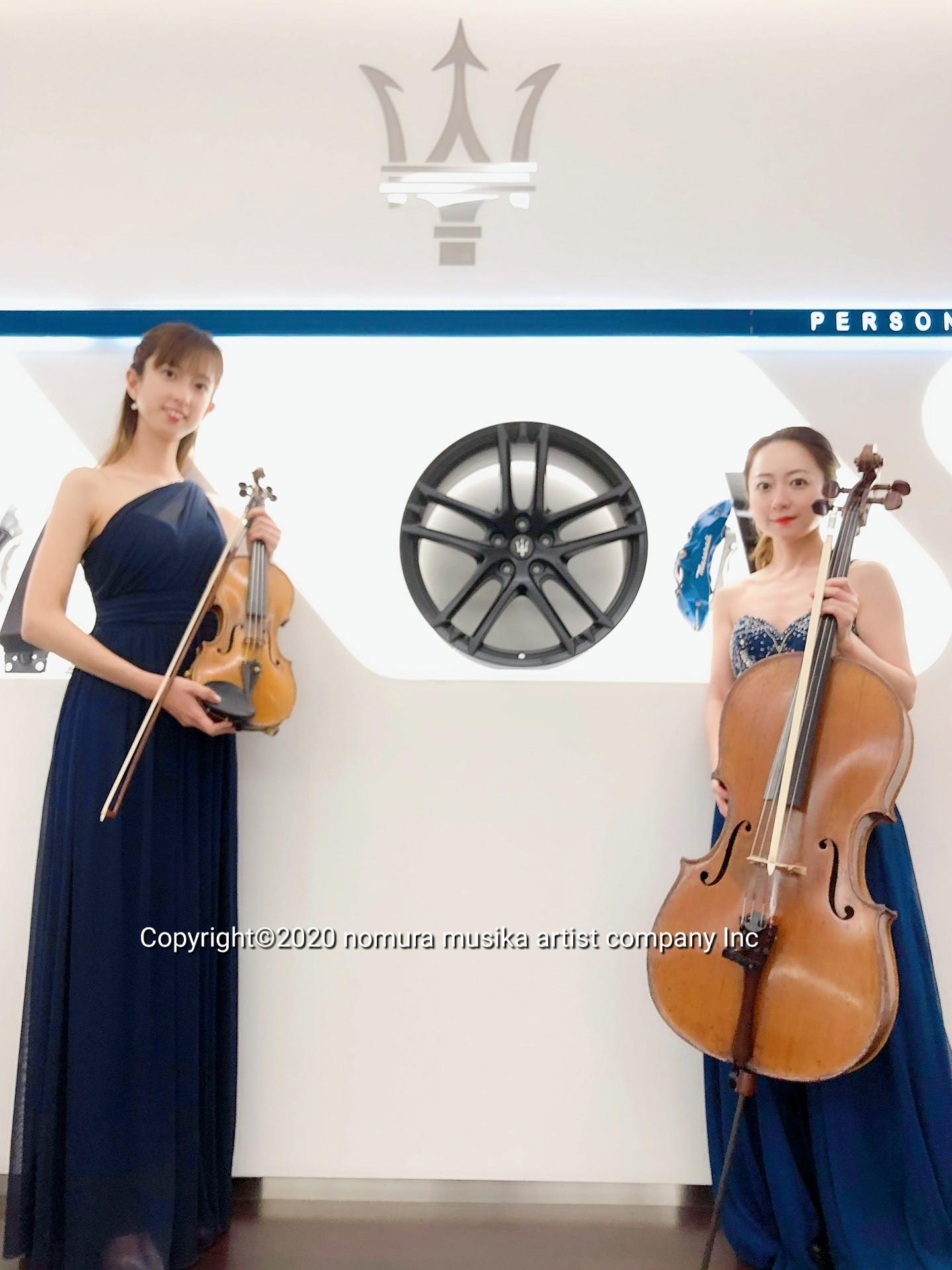 高級外車ロゴの前でヴァイオリニストとチェリストが楽器をもっている
